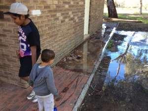 Image description: Children play in raw sewerage around a toilet block, Image - Amanda Albrecht