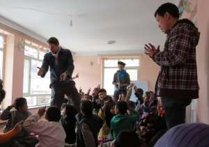 Children at the Afghan Peace Volunteer's Borderfree Street Kid's School learn from Ellis Brooks and Dr. Hakim about resolving conflicts peacefully. Photo - Dr. Hakim